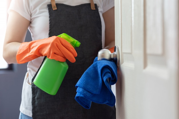 Female hands in orange rubber gloves cleaning on touching surface of door, doorknob with blue microfiber cleaning cloth and green antibacterial spray bottle.