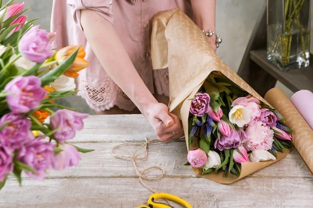 여성 손 포장지에 축제 꽃다발을 포장합니다. 인식 할 수없는 꽃집은 나무 배경에 워크샵에서 분홍색 모란과 야생화로 플로리스트 리를 조립합니다. 직장에서 여자