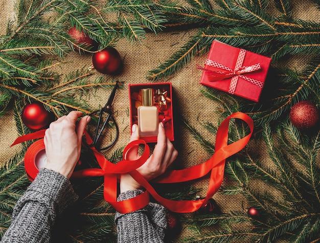 クリスマスの装飾の横にあるボックスに化粧品を包装する女性の手