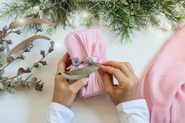 テーブルの上に風呂敷風の再利用可能なピンクの布でクリスマスギフトボックスを梱包する女性の手。