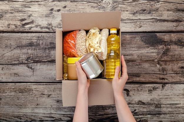 여성의 손은 나무 탁자에 주요 제품의 식품 품목과 함께 기부 상자를 포장합니다. 기부 식품 상자를 받는 사람 여자. 음식 배달 개념을 기부합니다. 기부 식료품 통조림 식품. 평면도.