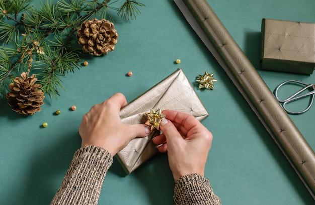 プレゼントボックスを梱包する女性の手。クリスマスツリーの枝、コーン、包装紙 Premium写真
