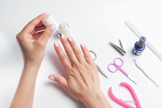 Женские руки красят ногти, рядом укладывают приспособления для ухода за ногтями. девушка делает маникюр. на белом фоне