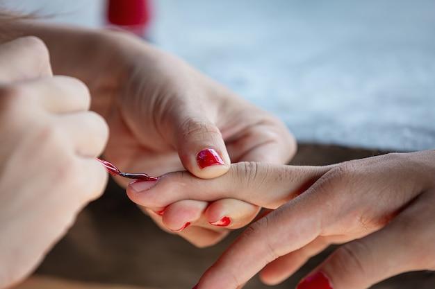 女性の手は赤い光沢で爪を描いた