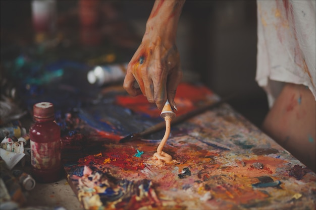 Female hands of the painter with brushes, paints, and a palette for drawing