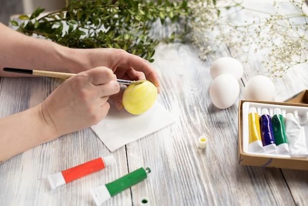여성 손 나무 테이블에 브러시로 노란색 달걀 그림. 부활절 준비