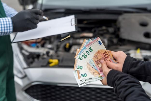 労働者への車のサービスにお金を払っている女性の手