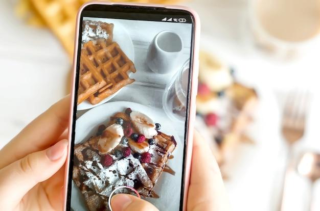 Женские руки фотографируют тарелку с домашними бельгийскими вафлями с сахарной пудрой
