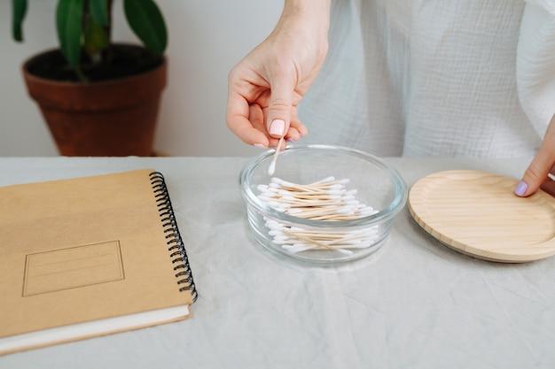 Женские руки вынимают экологически чистые ватные палочки из стеклянной тары. на столе деревянная крышка.