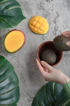 여성의 손은 대리석 표면에 있는 그릇에서 익은 아보카도를 따고 있습니다.