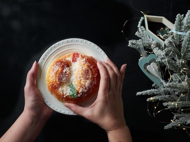 スペインの典型的なクリスマスケーキの小さなroscondereyesaを拾う女性の手