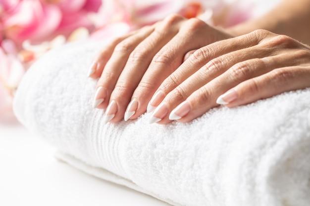 Женские руки положены на мягкое белое полотенце, готовое к маникюру в спа-салоне.
