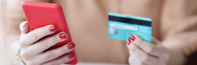 In female hands plastic credit card and smartphone