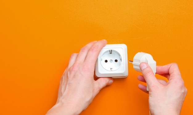 Female hands plug in power plug into electro outlet on orange background. minimalism. top view