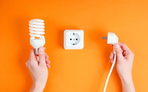 여성의 손에 오렌지 배경에 나선형 전구를 잡고 전원 플러그를 전기 콘센트에 꽂습니다. 미니멀리즘