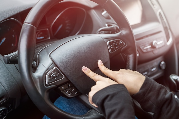 Female hands pointing with fingers on steering wheel