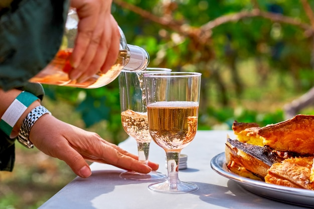 Female hands pour refreshing pink wine in a glass with cakes on the table