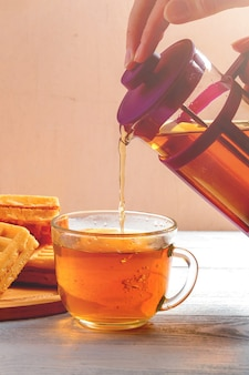 Female hands pour tea from brewer into mug on white wooden table with waffles.