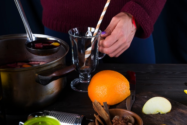 Female hands pouring hot mulled wine