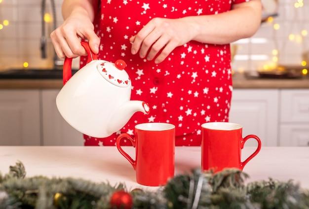 ティーポットから2つの赤いカップまたはマグカップにお茶を注ぐ女性の手