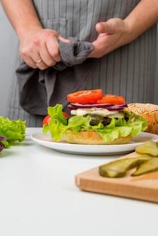 おいしいハンバーガーを準備する女性の手