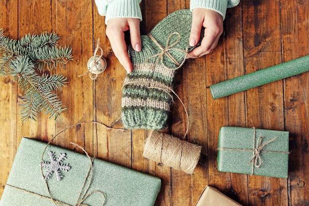 木製のテーブルでクリスマスの贈り物を準備する女性の手