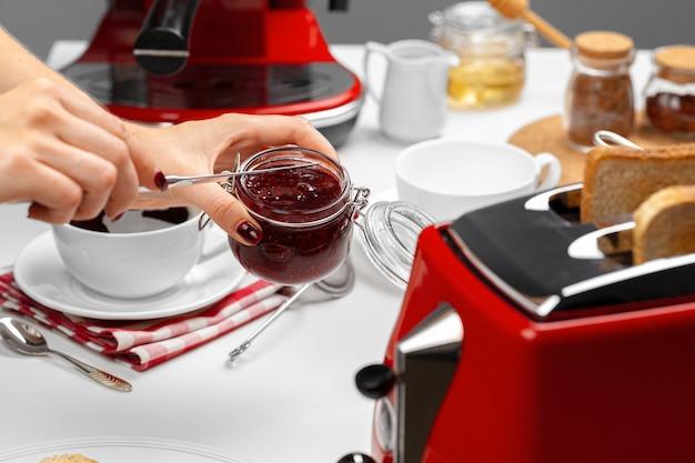 フルーツジャムとトーストを準備する女性の手