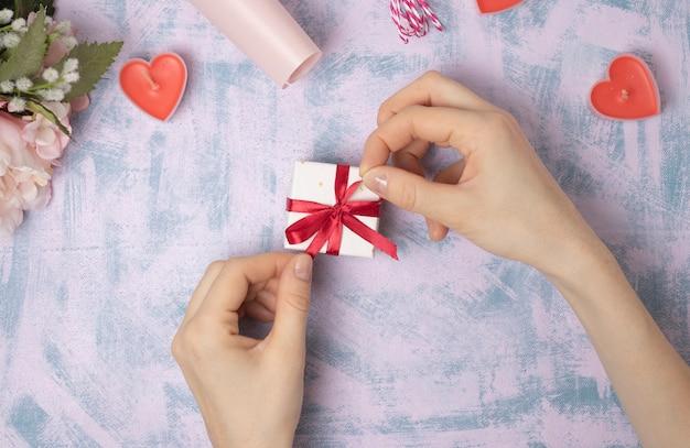 女性の手は明るい背景のギフトボックスに赤いリボンを引っ張る。クリスマスと新年または季節の挨拶。セレクティブフォーカス