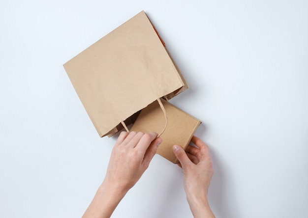 Female hands put cardboard box in paper bag on gray . top view