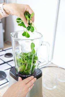 여성의 손은 신선한 녹색 시금치 잎을 믹서기 그릇에 넣습니다. 건강한 식단에 대한 아이디어, 비타민 그린 스무디 준비. 건강한 식단, 해독, 건강한 생활 방식의 개념.