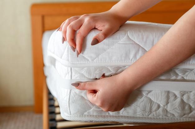 女性の手は、整形外科用マットレスの角に新しいマットレスパッドを置きます。自宅のベッドリネン。シートは柔らかく清潔なマットレスに着用されています。寝室の汚れで洗われたリネンマットレスパッドからの保護。