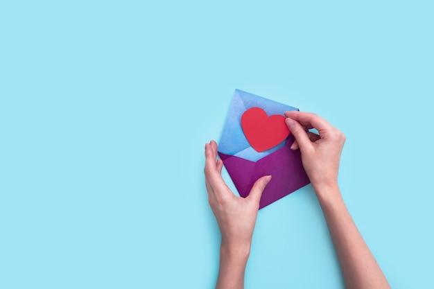 Женские руки вложили красное сердце из бумаги в фиолетовый конверт