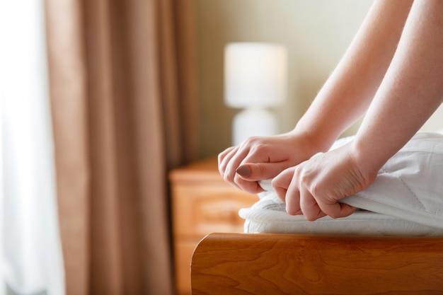 女性の手はマットレスの角に新しいマットレスパッドを置きます。自宅やホテルのベッドリネン。シートは柔らかく清潔なマットレスに着用されています。寝室の汚れで洗われたリネンマットレスパッドからの保護。