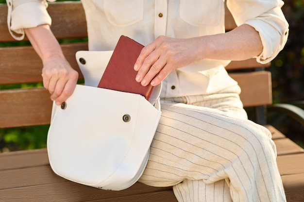 Female hands putting notebook in open bag