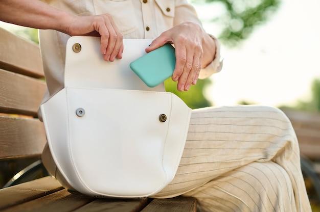Female hands putting smartphone in open bag