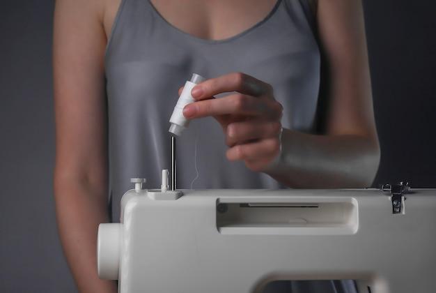 Женские руки кладут катушку ниток на швейную машину