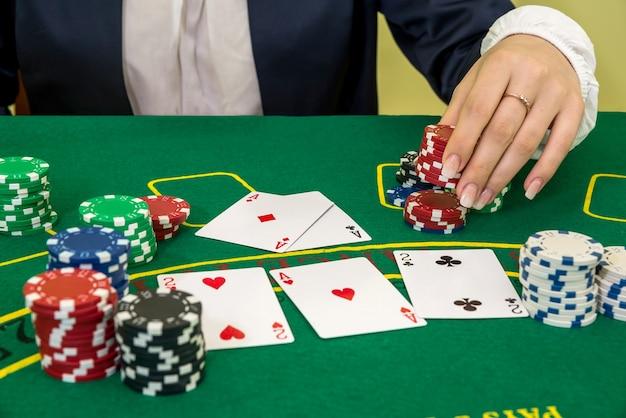 Женские руки тянутся к покерным фишкам, играют в карты в казино