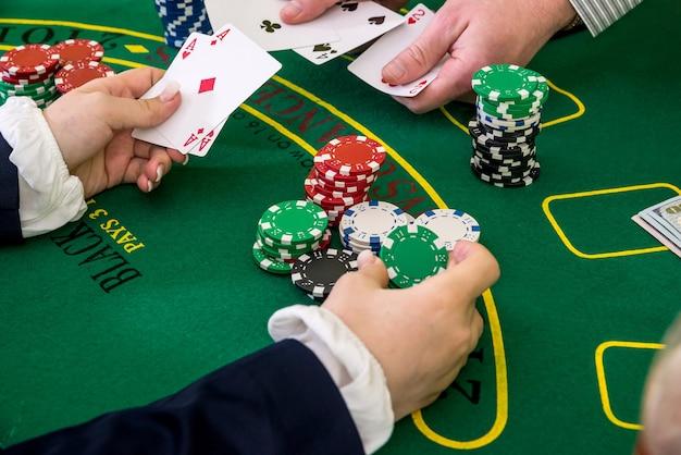 ポーカーチップ、カジノでトランプに手を伸ばす女性の手