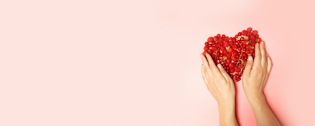 Female hands and red berries in the shape of a heart
