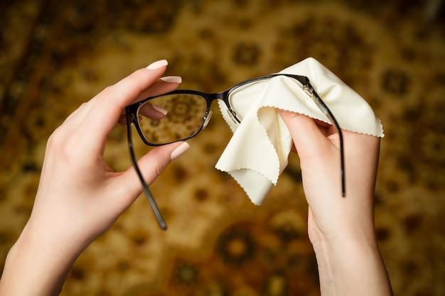 Женские руки протирают очки в черной оправе специальной губкой.