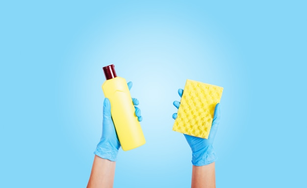 Female hands in rubber gloves hold detergent in a bottle and a sponge
