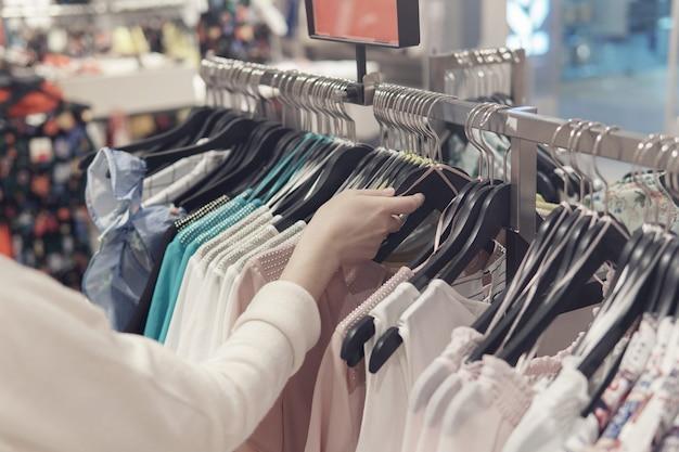 Женские руки роются в одежде в секонд-хенде.