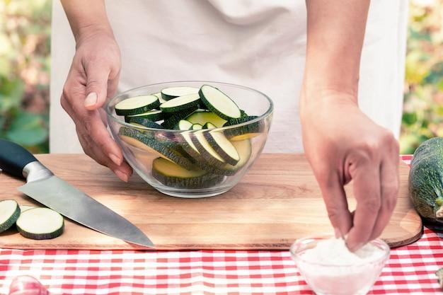 Женские руки соль нарезанный цуккини на деревянной доске