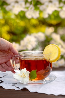 Женские руки подают стаканчик с чаем лимонная вышитая салфетка