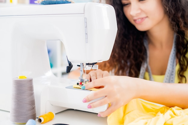 Female hands on sewing machine