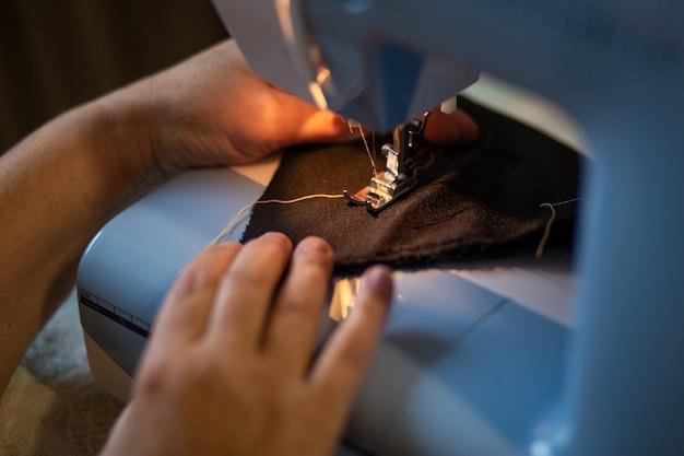 Женские руки шьет на швейной машинке