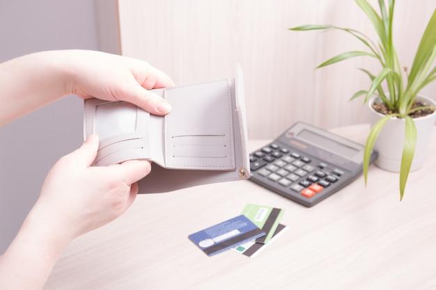 Женские руки качают содержимое кошелька на столе, перевернутый пустой бежевый кошелек