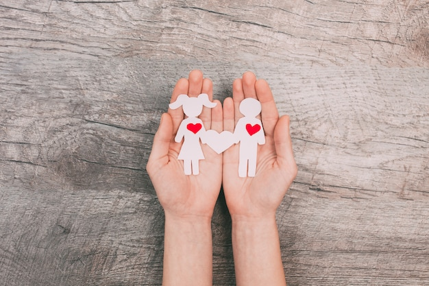 Female hands show two paper people, a man and a woman, on a wooden background