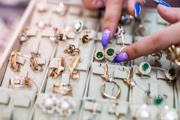 보석 컬렉션에 황금 반지를 보여주는 여성 손