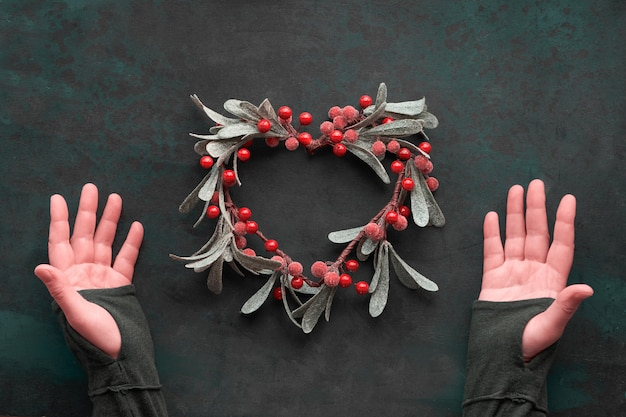 Female hands showing heart-shaped decorative mistletoe christmas wreath with red berries, flat lay